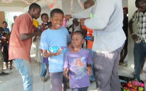 Team distributing water bottles, school supplies and candy to village children